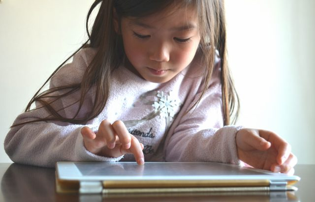 タブレットを見る小学生